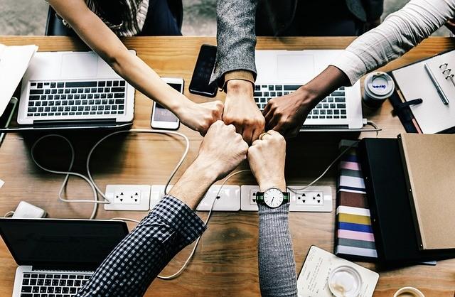 Cinq personnes regroupent leur main droite au centre d'une table composée d'ordinateurs, de smartphones et de dossiers
