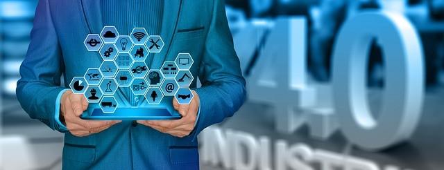 Personne tenant une tablette de laquelle s'échappe de nombreuses icones, devant un logo 3D indiquant : Industrie 4.0